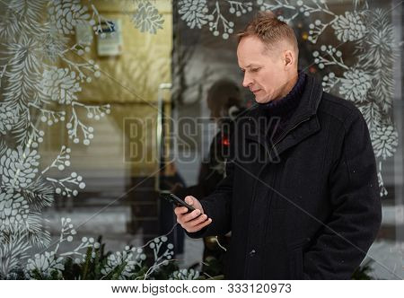 The Man With A Smartphone Is Standing On A Glass Showcase Background.