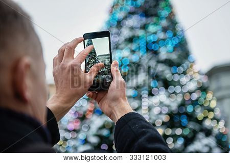 Man Is Photographing A Christmas Tree With The Smartphone.