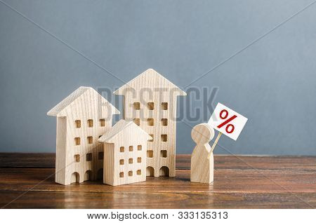 A Person With A Poster Is Standing Near The Houses. Mortgage To Purchase Affordable Comfortable Hous