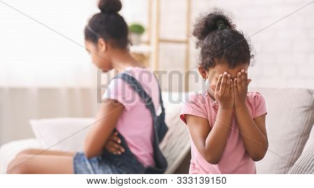 Family Conflict. Little African Girl Crying At Home, Being Ignored By Her Elder Sister, Panorama