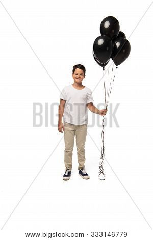 Cheerful Boy Looking At Camera While Holding Black Balloons On White Background