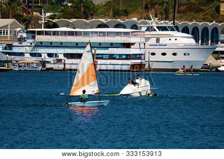 August 25, 2019 In Newport Harbor, Ca:  People Learning To Sail On Dinghy Sail Boats Including A Din