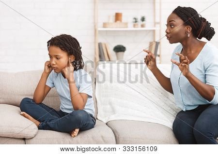 Family Conflict. Black Mom Lecturing Her Child For Bad Behavior, Little Girl Holding Her Ears Closed