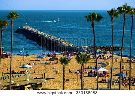 August 25, 2019 In Corona Del Mar, Ca:  Beachgoers Enjoying Activities On The Beach With A Rock Jett
