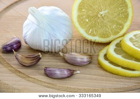 Extreme Close Up Of Lemon And Garlic Keep In A Bowl. A Hand Picking A Cut Lemon.