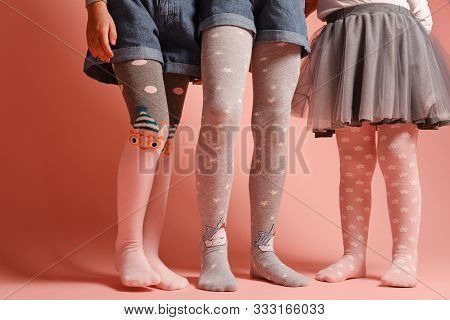 Girlish Legs In Pantyhose On A Pink Background. A Collection Of Childrens Tights For Girls. A Variet