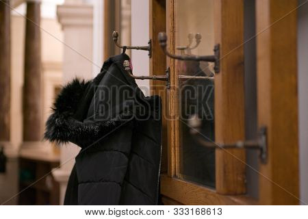 Black Winter Coat Hung On Vintage Wooden Ornate  Coat Hanger Hooks Around Ornate Mirror