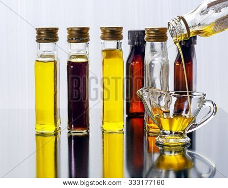 Vegetable Oil In Glass Transparent Bottles With Screw Caps. Bottles Of Vegetable Oil Reflected On Th