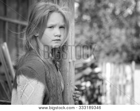 Portrait Of A Sad Girl. The Child Is Waiting For Someone. Concept Of Loneliness, Inner Fears Of Chil