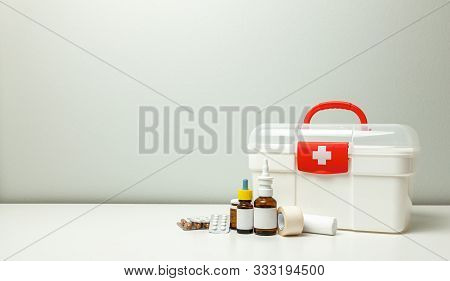 First Aid Kit. White Box With A Cross And A Red Fastener And Pills With Medicine Bottles On A Gray B