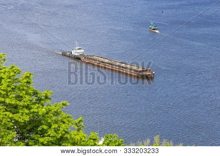 A Tug Boat Hauls A Large, Empty Barge Down Wide Dnipro River Dirung Sunny Day. Seafaring, Navigation