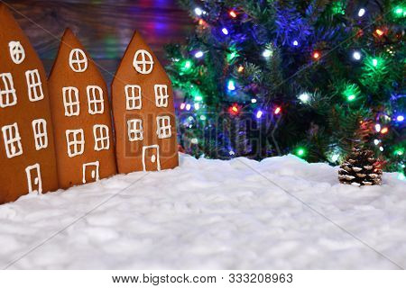 The Hand-made Eatable Gingerbread Houses, Snow Decoration, New Year Tree With Garland In Background