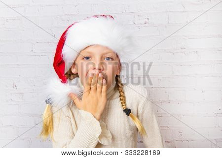 cute surprised little Santa hat girl at christmas