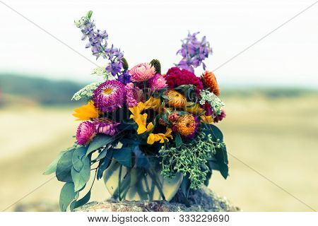 Bouquet Of Chrysanthemums, Sunflowers And Eucalyptus On A Large Stone On A Sandy Beach, In Half Moon