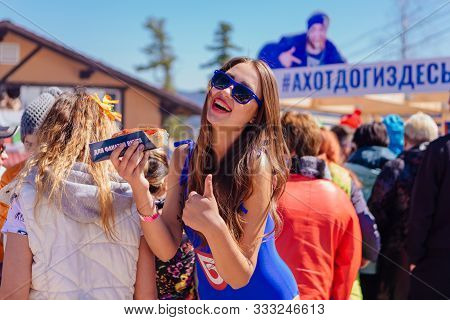Sheregesh, Kemerovo Region, Russia - April 22, 2017: Young Happy Pretty Woman Eating Hotdog