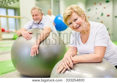 Vital senior couple with gym ball pauses at the back school in physiotherapy