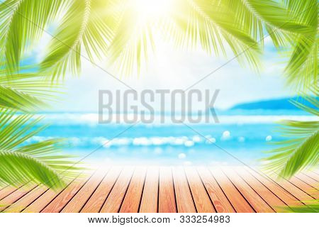 Blur Tropical Beach With Bokeh Sun Light Wave And Palm Tree On Copy Space Empty Old Wood Table Abstr