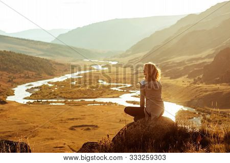 Slim Girl Sits On Big Rock And Enjoys The View Of Sunset Mountains And River