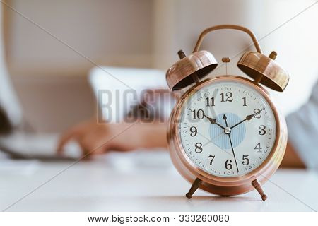 Alarm Clock On White Table Background With Businessman Working With Laptop.time Management And Punct
