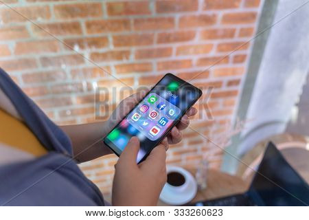Chiang Mai, Thailand - Oct.18,2019: Woman Holding Xiaomi Mi Mix 3 With Icons Of Social Media On The