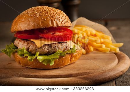 Home Made Hamburger With Beef, Onion, Tomato, Lettuce And Cheese. Fresh Burger Close Up On Wooden Ru