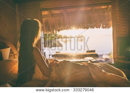 Luxury hotel room honeymoon travel holiday at high end resort stay - Girl waking up in bed looking at ocean view in overwater bungalow in Bora Bora, Tahiti ,French Polynesia.