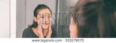 Face wash young Asian woman applying scrub exfoliating skin in beauty skincare routing morning lifestyle - Bathroom mirror panoramic banner panorama.