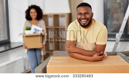 moving, repair and real estate concept - happy african american couple with stuff in cardboard boxes at new home