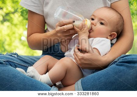 family, babyhood and people concept - close up of mother feeding baby with milk formula from bottle over green natural background
