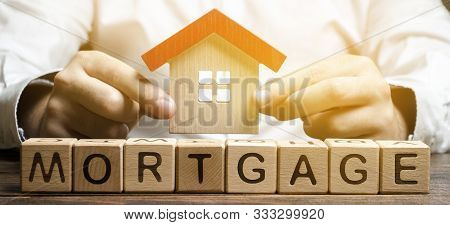 Wooden Blocks With The Word Mortgage And House In The Hands Of A Businessman. The Concept Of Buying