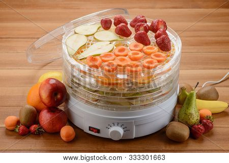 Drying And Preserving Fruits With An Electronic Dehydrator. Kitchen Tool And Heap Of Various Fruits