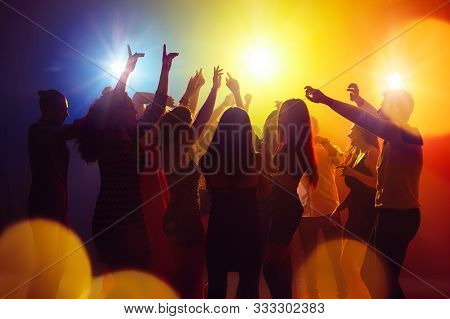 Friends. A Crowd Of People In Silhouette Raises Their Hands On Dancefloor On Neon Light Background.