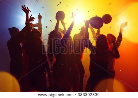 Corporate. A Crowd Of People In Silhouette Raises Their Hands On Dancefloor On Neon Light Background