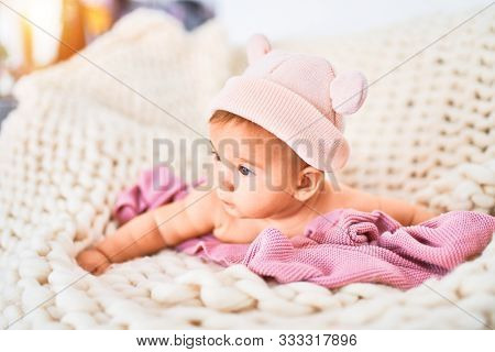 Adorable baby lying down over blanket on the sofa at home. Newborn wearing fanny hat relaxing and resting comfortable