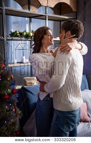 Boyfriend And Girlfriend In Sweaters Smiling And Hugging At Christmastime