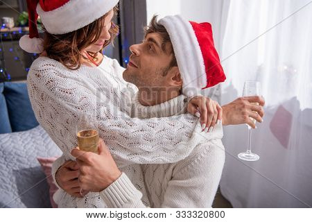 Boyfriend And Girlfriend In Santa Hats Hugging And Holding Champagne Glasses At Christmastime