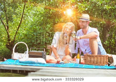 Young couple having picnic while sitting in pier at lakeshore with yellow lens flare