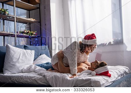 Smiling Girlfriend In Santa Hat Sitting On Boyfriend And Hugging Him At Christmastime