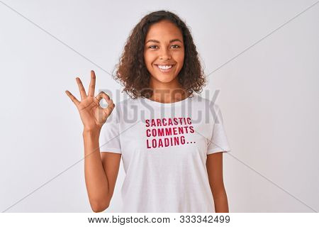 Brazilian woman wearing fanny t-shirt with irony comments over isolated white background doing ok sign with fingers, excellent symbol