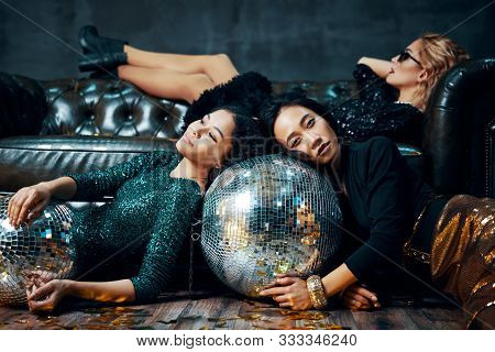 Crazy Party. Pretty Multiethnic Young Women Relaxed After Party, Lying Down On The Floor And Sofa. C