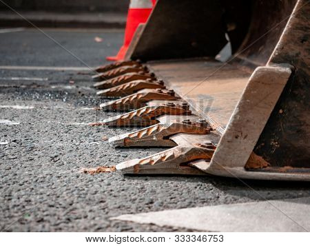 Excavator With Hydraulic Bucket Stands On Asphalt Surface Carriageway. Steel Bucket Tines Close-up.
