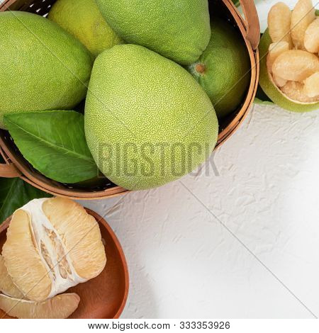 Fresh Pomelo, Pummelo, Grapefruit, Shaddock On White Cement Background In Bamboo Basket. Autumn Seas