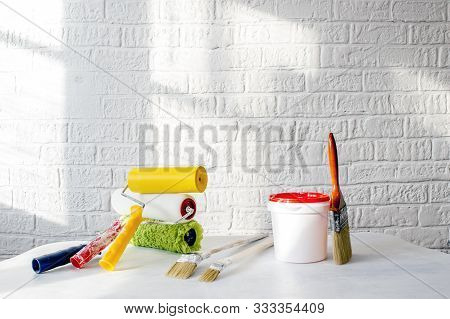 A Bucket Of Paint, A Set Of Rollers And Brushes On A White Table Against A White Wall Decorated With