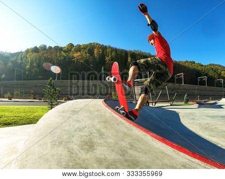 Young Skateboarder Making Tricks On Skateboard In Skatepark