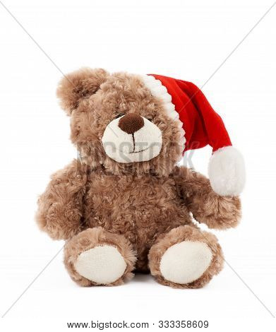 Little Cute Brown Teddy Bear With In A Red Christmas Hat Sits On An Isolated White Background, Holid