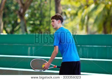 Young Man Playing Tennis On Open Court