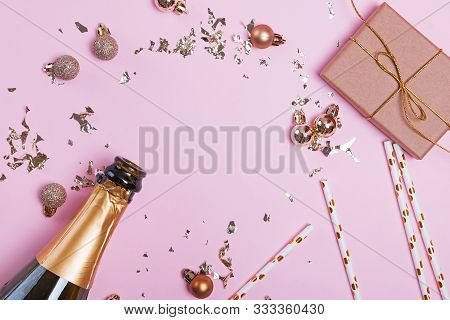 Creative Composition With Golden Colored Decor, Sparkles Asn Campagne Bottle On Pink Background.