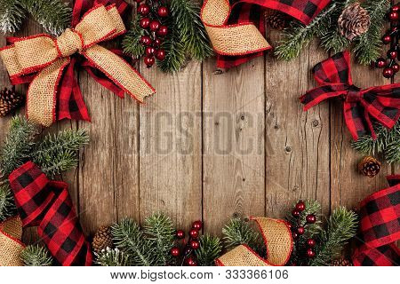 Christmas Frame With Red And Black Checked Buffalo Plaid Ribbon, Burlap And Tree Branches. Top View