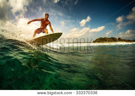 Surfer rides the ocean wave in tropics.