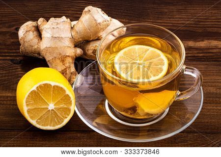 Cup Of Ginger Tea With Lemon, Honey And Ginger Root On A Wooden Background.